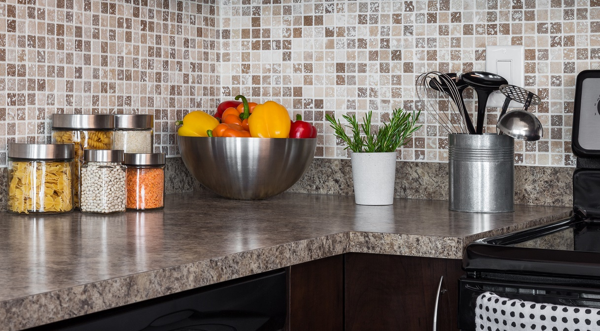 Food ingredients and green herbs on modern kitchen countertop.